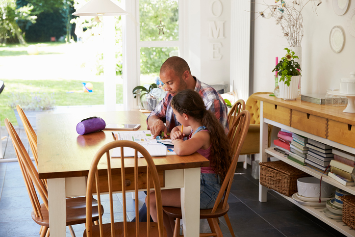Father and daughter studying at table