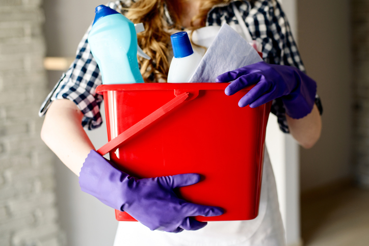 Woman holding bucket of cleaning items