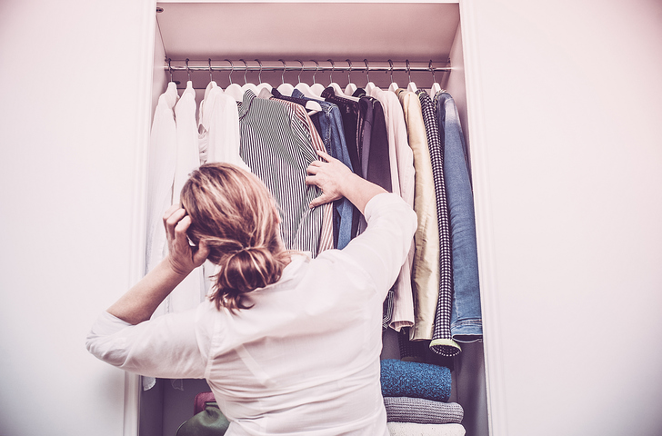 Woman in closet deciding what to wear
