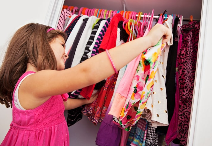 child in closet picking out clothes decluttering