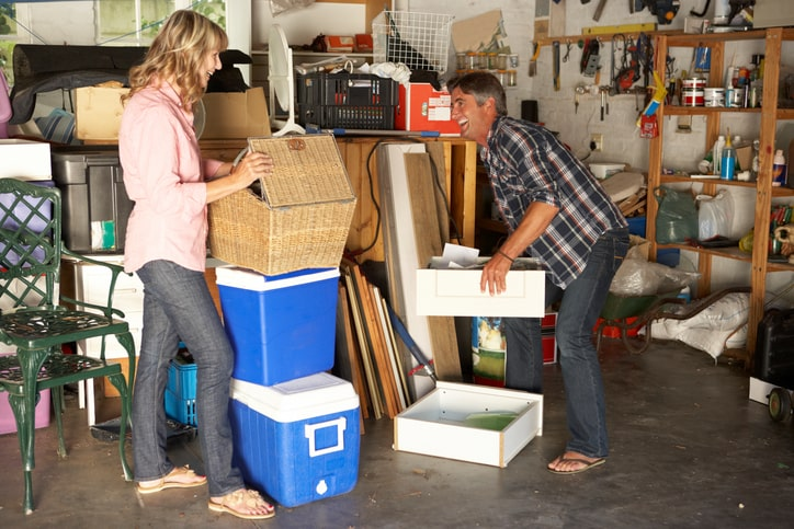 Couple smiles as they sort through items in their garage.