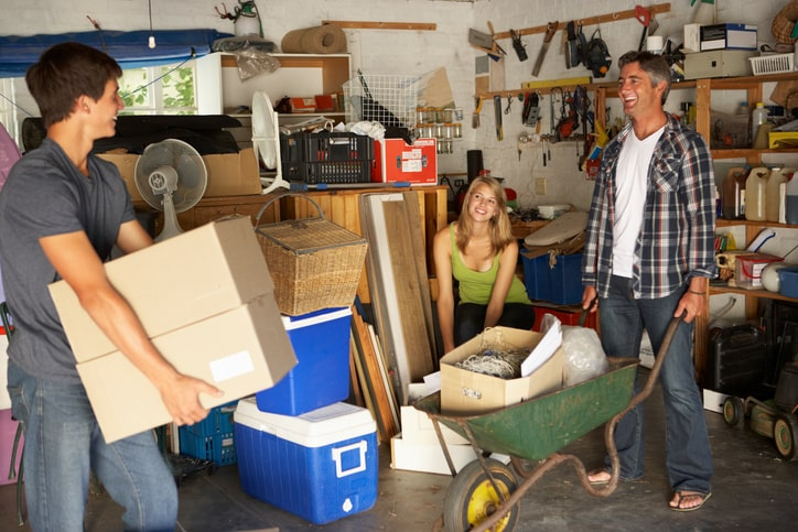 Family smiles as they sort through the items in their garage.