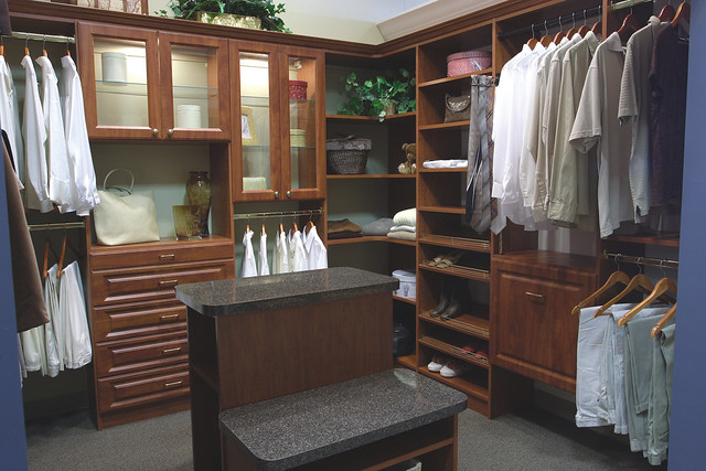 A custom closet storing organized men's and women's clothing with a dark wood design.