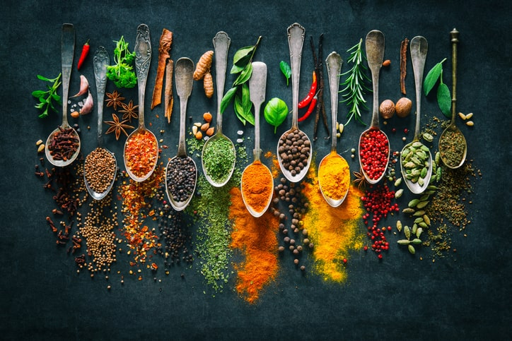 Herbs and spices in spoons and on dark background