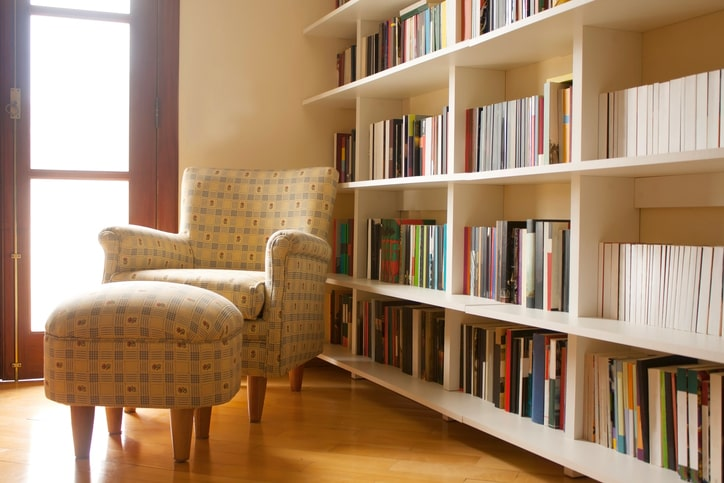 A home reading room with white bookshelves